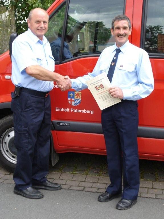 Der Vorsitzende des KFV, Gerhard Bingel, verleiht Achmed Rommersbach die Ordensspange des KFV.